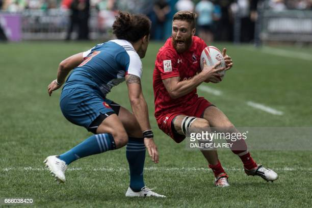 Canada's Luke McCloskey runs with the ball past France's Pierre Gilles Lakafia during the second day of the Hong Kong Rugby Sevens tournament on...