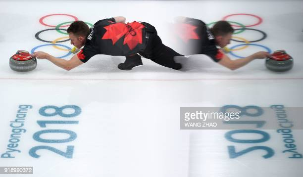 TOPSHOT Canada's Marc Kennedy is reflected in a window pane as he throws the stone during the curling men's round robin session between Canada and...