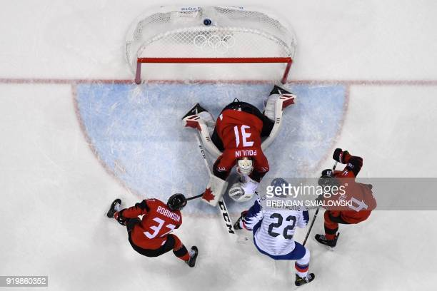 Canada's Mat Robinson South Korea's Mike Testwuide and Canada's Chris Lee watch as Canada's Kevin Poulin makes a save in the men's preliminary round...