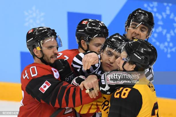 TOPSHOT Canada's Maxim Lapierre grabs Germany's Frank Mauer in the men's semifinal ice hockey match between Canada and Germany during the Pyeongchang...