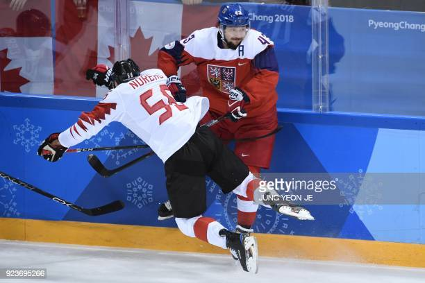 Canada's Maxim Noreau and Czech Republic's Jan Kovar collide in the men's bronze medal ice hockey match between the Czech Republic and Canada during...