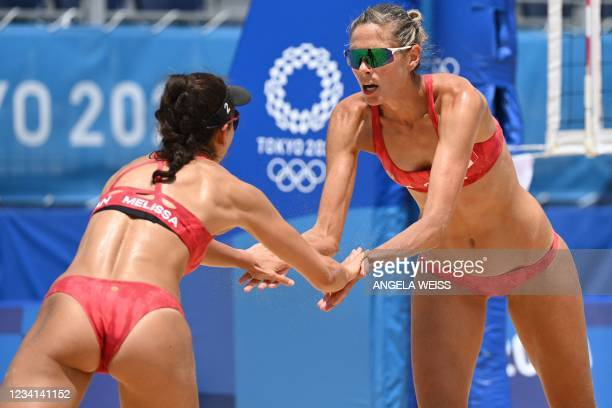 Canada's Melissa Humana-Paredes and Sarah Pavan celebrate a point in their women's preliminary beach volleyball pool A match between Canada and the...