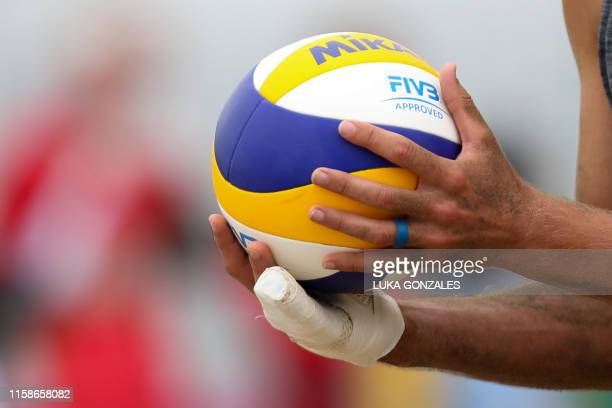 Canada's Michael Plantinga holds up the ball during a Lima 2019 PanAmerican Games men's beach volleyball match against Argentina in Lima Peru on July...