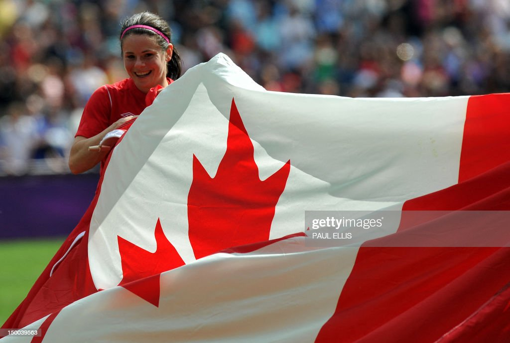 Canada's midfielder Diana Matheson holds a giant Canadian flag as the celebrates at the end of the women's football match for bronze of the London 2012 Olympic Games at the City of Coventry stadium on August 9, 2012 in Coventry. Canada defeated France 1-0.