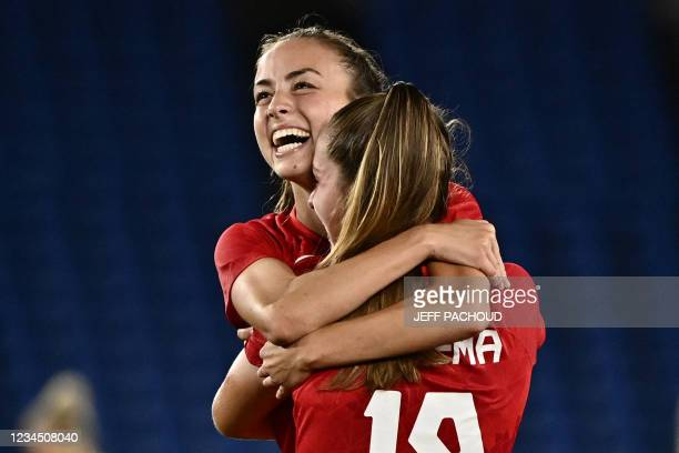 Canada's midfielder Julia Grosso hugs forward Jordyn Huitema after scoring the winning penalty during the penalty shoot-out of the Tokyo 2020 Olympic...