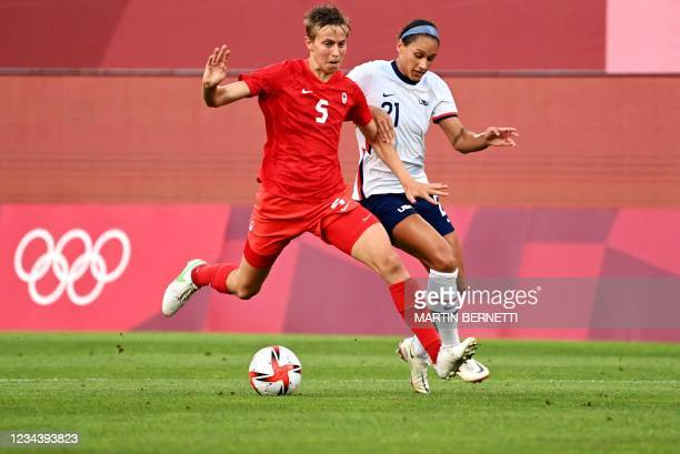 Canada's midfielder Quinn is marked by USA's forward Lynn Williams during the Tokyo 2020 Olympic Games women's semi-final football match between the...