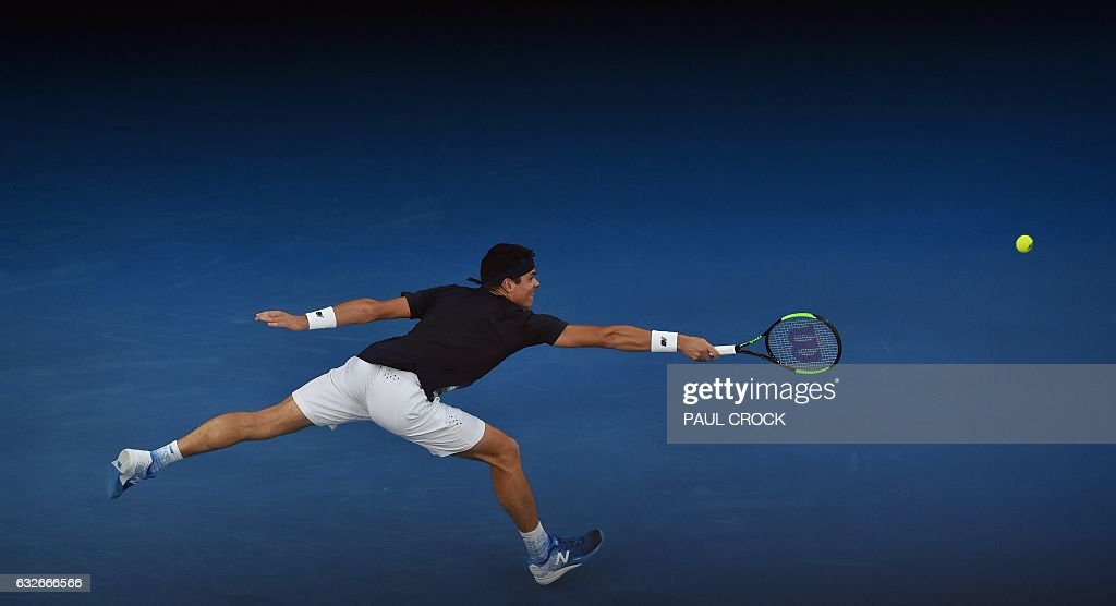 TOPSHOT - Canada's Milos Raonic hits a return against Spain's Rafael Nadal during their men's singles quarter-final match on day ten of the Australian Open tennis tournament in Melbourne on January 25, 2017. / AFP / PAUL