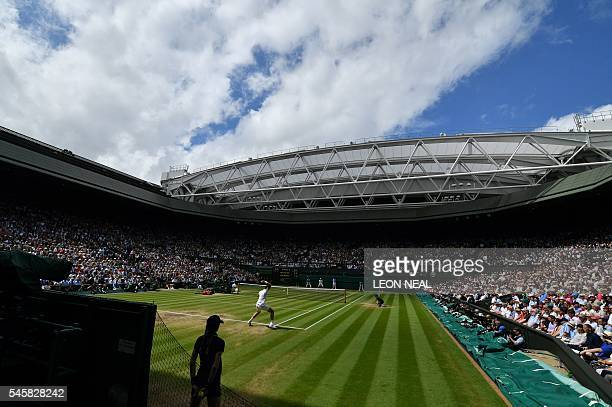 TOPSHOT Canada's Milos Raonic returns to Britain's Andy Murray during the men's singles final match on the last day of the 2016 Wimbledon...