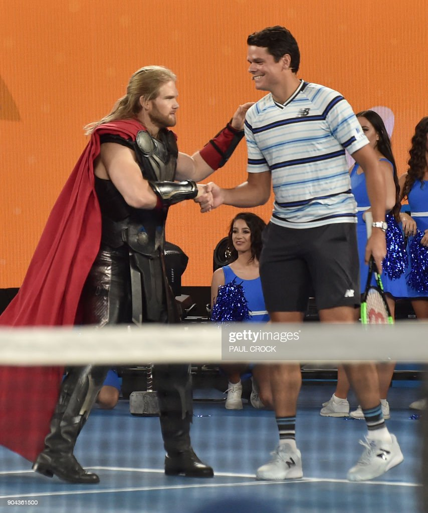 Canada's Milos Raonic shakes hands with an actor dressed as Marvel superhero character Thor during a Kids Day event ahead of the Australian Open tennis tournament in Melbourne on January 13, 2018. /