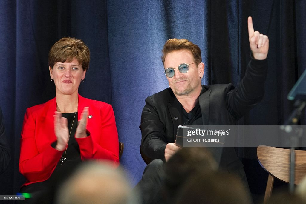Canada's Minister of International Development and La Francophonie, Marie-Claude Bibeau applauds as U2 singer Bono gestures during ONEs Poverty is Sexist town hall meeting in Montreal, Quebec, September 17, 2016. / AFP / Geoff Robins