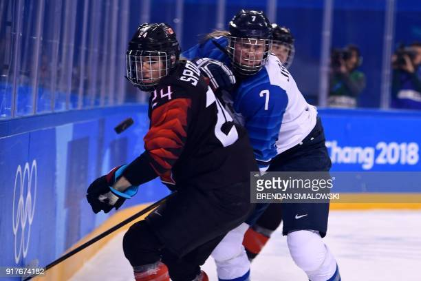 Canada's Natalie Spooner and Finland's Mira Jalosuo fights for the puck during the final period of the women's preliminary round ice hockey match...