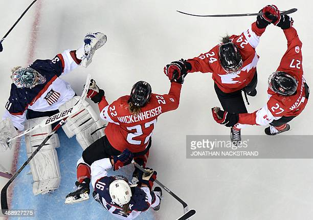 Canada's Natalie Spooner celebrates with team mates after scoring a goal during the Women's Ice Hockey Group A match between Canada and USA at the...