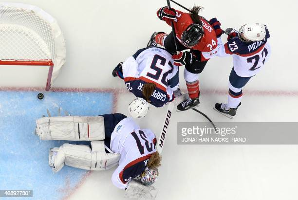 Canada's Natalie Spooner scores a goal during the Women's Ice Hockey Group A match between Canada and USA at the Sochi Winter Olympics on February 12...