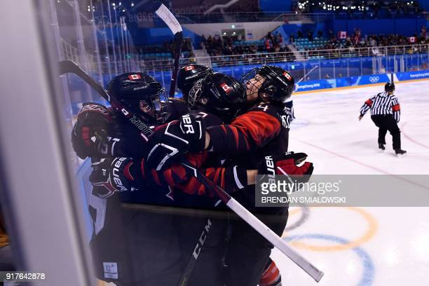 Canada's players celebrate after scoring during the first period of the women's preliminary round ice hockey match between Canada and Finland during...