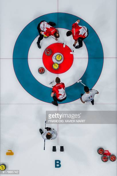 Canada's players Marc Kennedy Brent Laing and Ben Hebert follow their stone during the curling men's round robin session between Canada and Italy at...