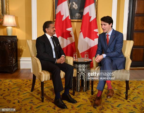 Canada's Prime Minister Justin Trudeau chats with the chairman of Indian multinational conglomerate Mahindra Group Anand Mahindra during their...
