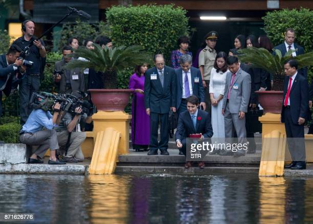 Canada's Prime Minister Justin Trudeau feeds fish at the former residence of late president Ho Chi Minh inside the presidential palace ground in...