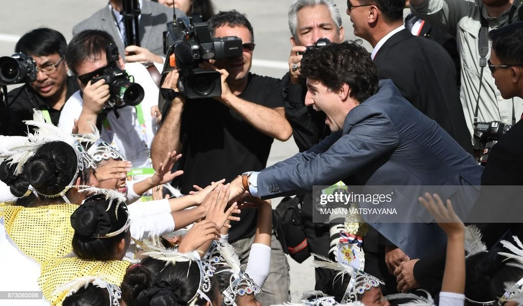 TOPSHOT - Canada's Prime Minister Justin Trudeau (C) greets performers upon arriving at Clark International airport in Pampanga province, north of Manila on November 12, 2017 to attend the 31st Association of South East Asian Nations (ASEAN) Summit. World leaders arrive in the Philippines' capital for two days of summits beginning on November 13. /