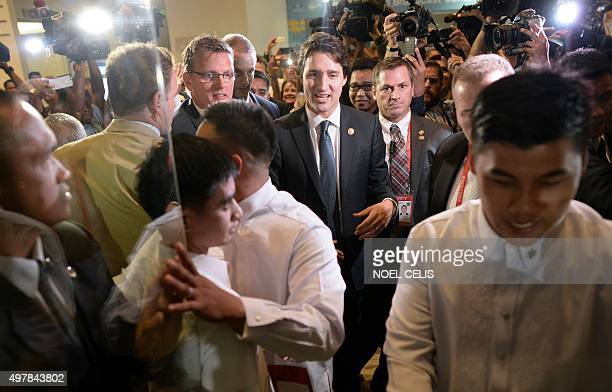 Canada's Prime Minister Justin Trudeau is surrounded by press and volunteers as he leaves after a press conference at the AsiaPacific Economic...