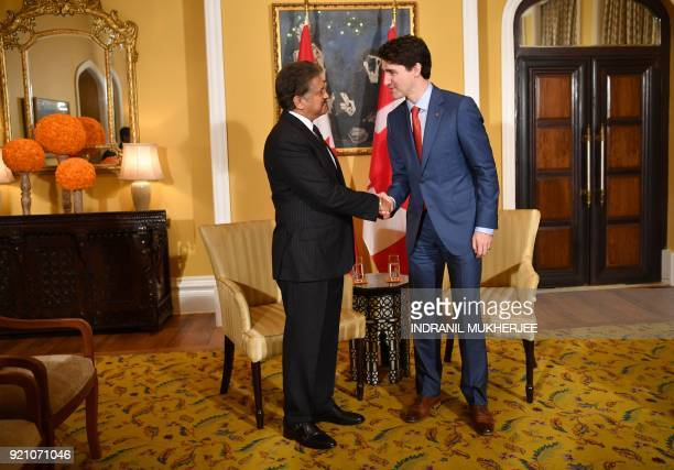 Canada's Prime Minister Justin Trudeau shakes hands with the chairman of Indian multinational conglomerate Mahindra Group Anand Mahindra during their...