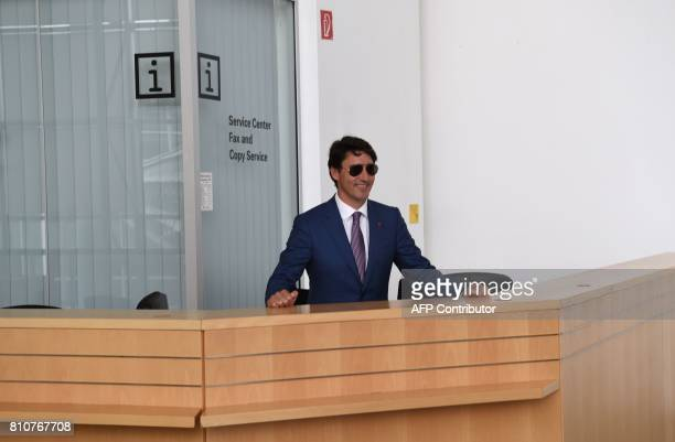 Canada's Prime Minister Justin Trudeau sits behind a service point as he jokes with journalists during the G20 summit in Hamburg northern Germany on...