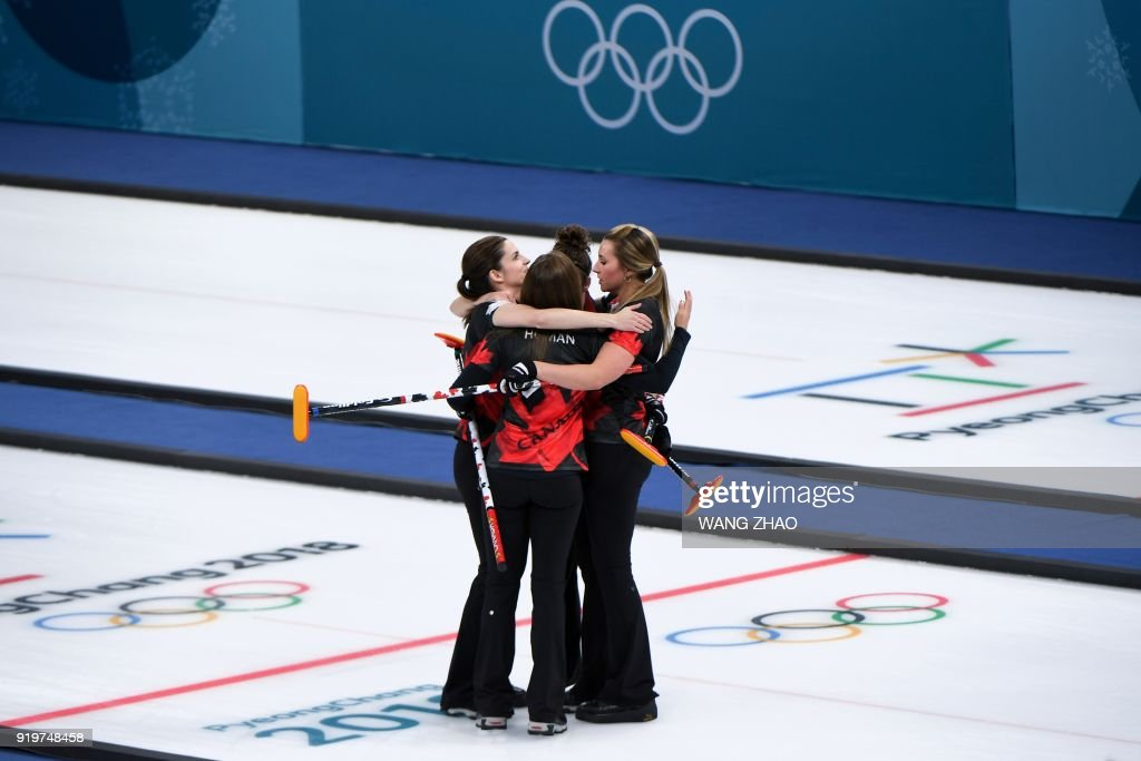 TOPSHOT - Canada's Rachel Homan (C) celebrates with her teammates after winning the curling women's round robin session between Canada and Switzerland during the Pyeongchang 2018 Winter Olympic Games at the Gangneung Curling Centre in Gangneung on February 18, 2018. / AFP PHOTO / WANG Zhao