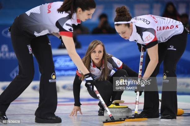 Canada's Rachel Homan watches the stone as teammates Lisa Weagle and Joanne Courtney clear a path during the gold medal match against Russia at the...