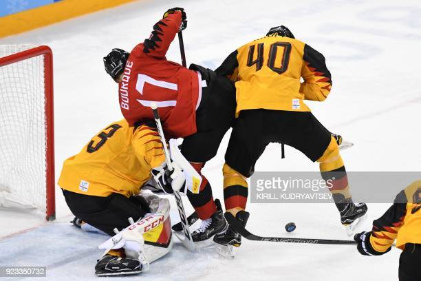 TOPSHOT Canada's Rene Bourque fights with Germany's Danny aus den Birken and Bjorn Krupp for the puck in the men's semifinal ice hockey match between...