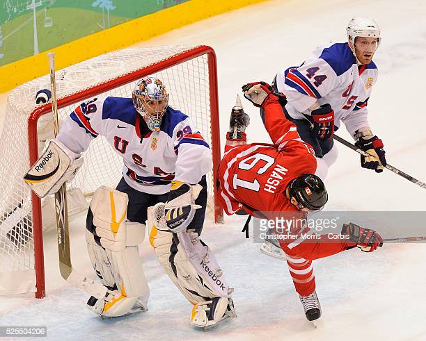 Canada's Rick Nash is put off balance as USA's Ryan Miller and USA's Brooks Orpik defend during Canada vs. USA preliminary round Ice Hockey action,...