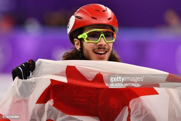 TOPSHOT Canada's Samuel Girard celebrates his gold win in the men's 1000m short track speed skating A final event during the Pyeongchang 2018 Winter...