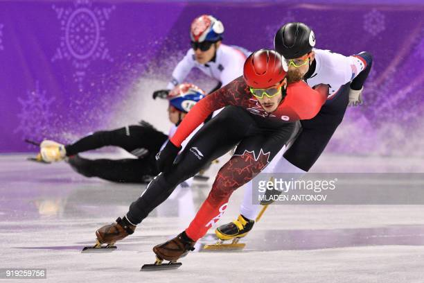 TOPSHOT Canada's Samuel Girard leads in front of USA's JohnHenry Krueger as South Korea's Seo Yira and compatriot Lim Hyojun crash in the men's 1000m...