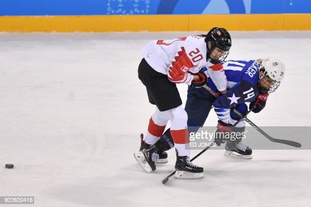 Canada's Sarah Nurse and USA's Brianna Decker skate past the puck in the women's gold medal ice hockey match between the US and Canada during the...
