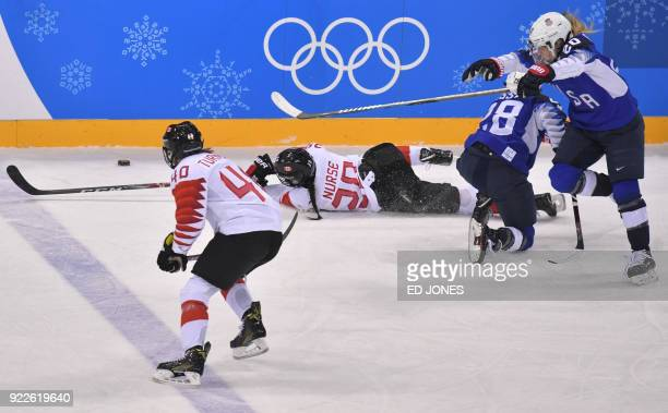 Canada's Sarah Nurse falls on the ice as teammate Blayre Turnbull USA's Amanda Kessel and Hannah Brandt watch in the women's gold medal ice hockey...