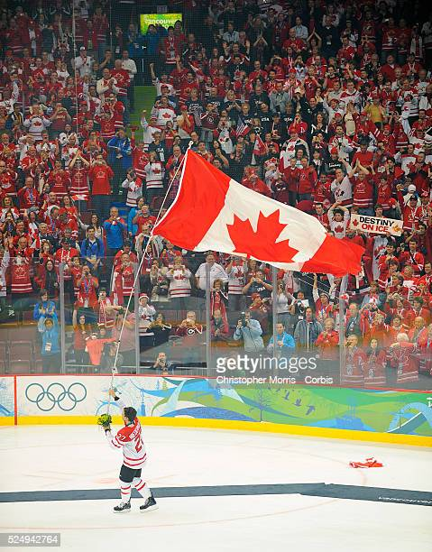 Canada's Scott Niedermayer carries the Canadian flag to celebrate after Team Canada's 3-2 overtime win over the USA in the Gold medal game at Canada...