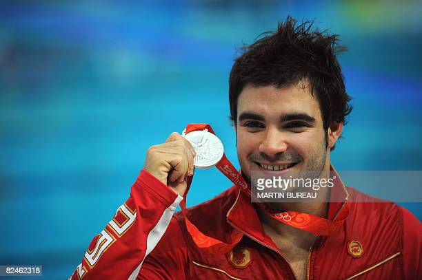 Canada's silver medalist Alexandre Despatie poses on the podium of the men's 3m springboard diving final at the National Aquatics Center during the...