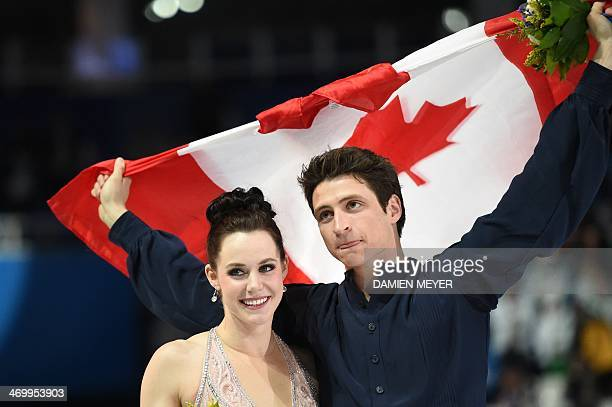 Canada's silver medalist Scott Moir and Tessa Virtue pose during the Figure Skating Ice Dance Flower Ceremony at the Iceberg Skating Palace during...