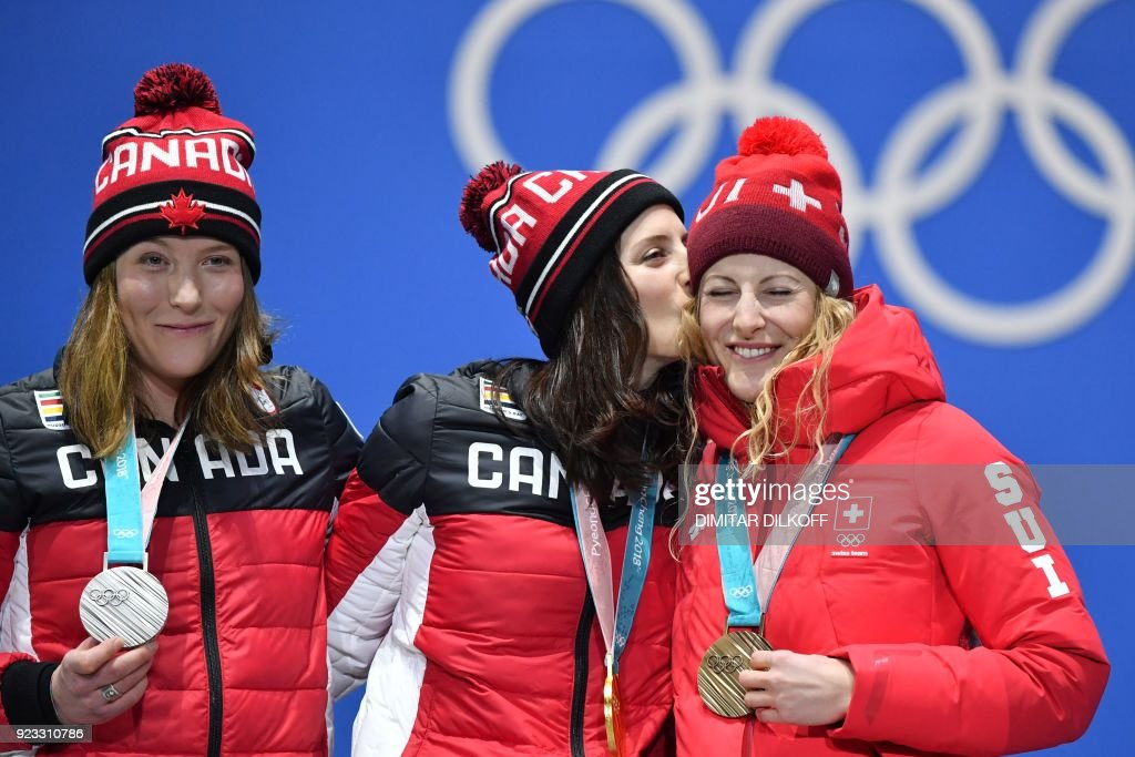 Canada's silver medallist Brittany Phelan, Canada's gold medallist Kelsey Serwa and Switzerland's bronze medallist Fanny Smith pose on the podium during the medal ceremony for the freestyle skiing Women's Ski Cross at the Pyeongchang Medals Plaza during the Pyeongchang 2018 Winter Olympic Games in Pyeongchang on February 23, 2018. / AFP PHOTO / Dimitar DILKOFF