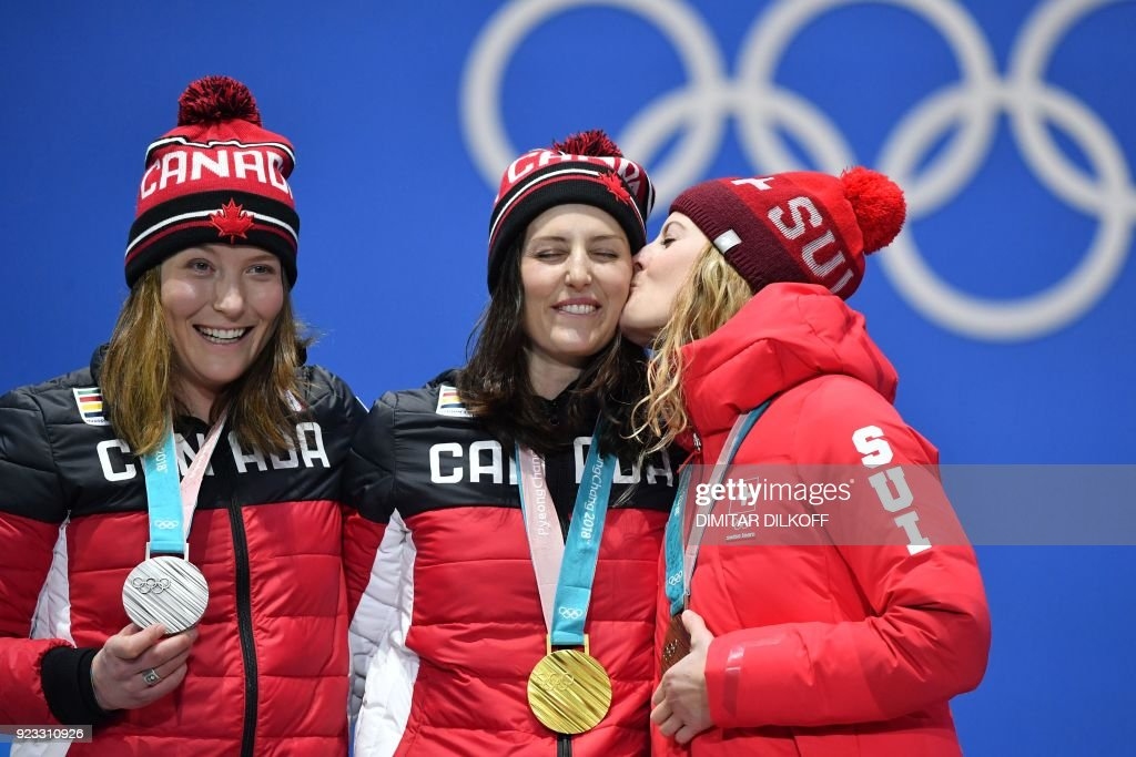 TOPSHOT - Canada's silver medallist Brittany Phelan, Canada's gold medallist Kelsey Serwa and Switzerland's bronze medallist Fanny Smith pose on the podium during the medal ceremony for the freestyle skiing Women's Ski Cross at the Pyeongchang Medals Plaza during the Pyeongchang 2018 Winter Olympic Games in Pyeongchang on February 23, 2018. / AFP PHOTO / Dimitar DILKOFF