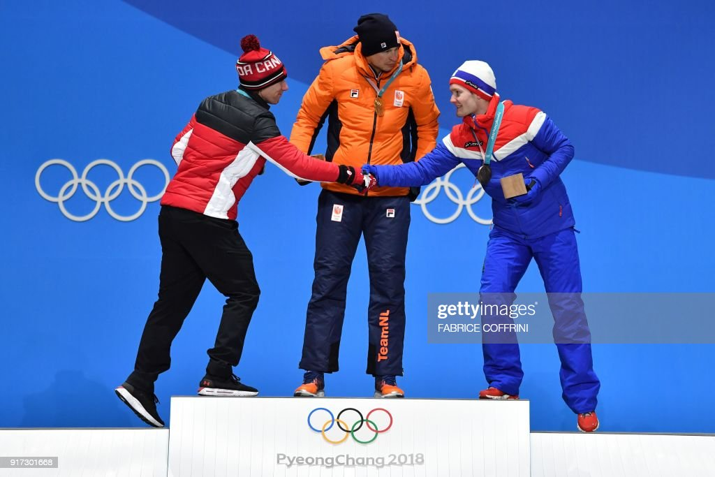 Canada's silver medallist Ted-Jan Bloemen, Netherlands' gold medallist Sven Kramer and Norway's bronze medallist Sverre Lunde Pedersen greet each other on the podium during the medal ceremony for the men's 5000m speed skating at the Pyeongchang Medals Plaza during the Pyeongchang 2018 Winter Olympic Games in Pyeongchang on February 12, 2018. / AFP PHOTO / Fabrice COFFRINI