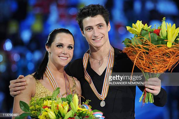 Canada's Tessa Virtue and Scott Moir pose on the ice rink with their medals during the victory ceremony of the ice dance category of the ISU World...