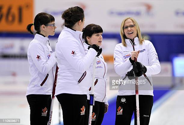 Canada's third Kim Schneider, second Tammy Schneider, lead Heather Kalenchuk and skip Amber Holland chat as an official measures the stones during...