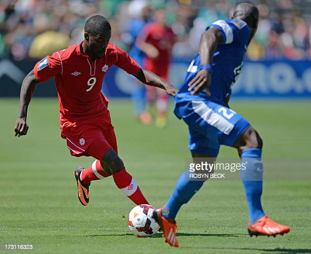Canada's Tosaint Ricketts vies with Martinique's Sebastien Cretinoir during the 2013 CONCACAF Gold Cup opener on July 7 2013 at the Rose Bowl in...