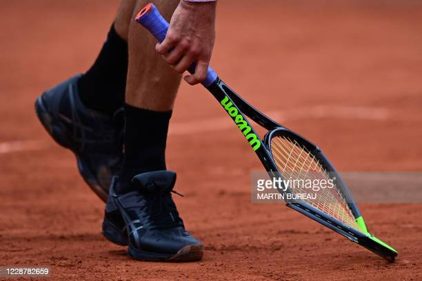 Canada's Vasek Pospisil picks up his racket after smashing it on the ground as he plays against Italy's Matteo Berrettini during their men's singles...