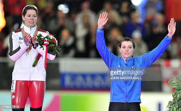 Canada's winner Christine Nesbitt applauds third placed Heather Richardson of the US on the podium of the women's 1000m competition of the...