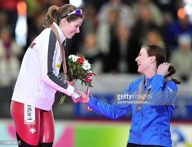 Canada's winner Christine Nesbitt congratulates third placed Heather Richardson of the US on the podium of the women's 1000m competition of the...
