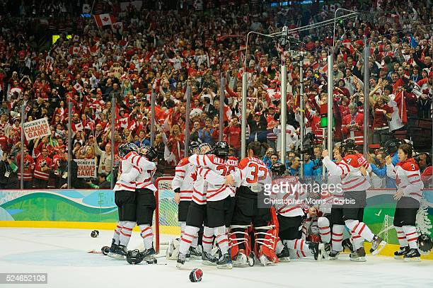 Canada's women's hockey team members celebrate after beating The United States to win the gold medal in hockey at Canada Hockey Place, day 14 of the...