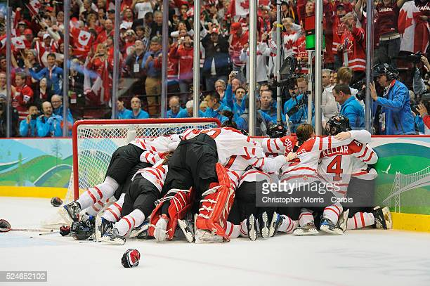Canada's women's hockey team members jump on goalie Shannon Szabados after beating The United States to win the gold medal in hockey at Canada Hockey...