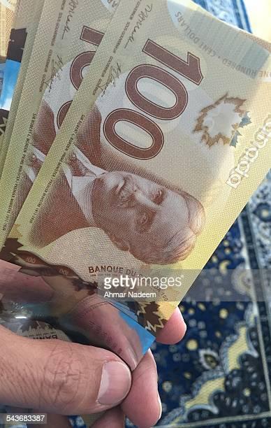 Canadian 100 Dollar Bills in hand