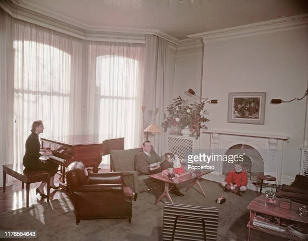 Canadian actor Alexander Knox seated with his wife actress Doris Nolan and son Andrew in the living room of their home in England in February 1958