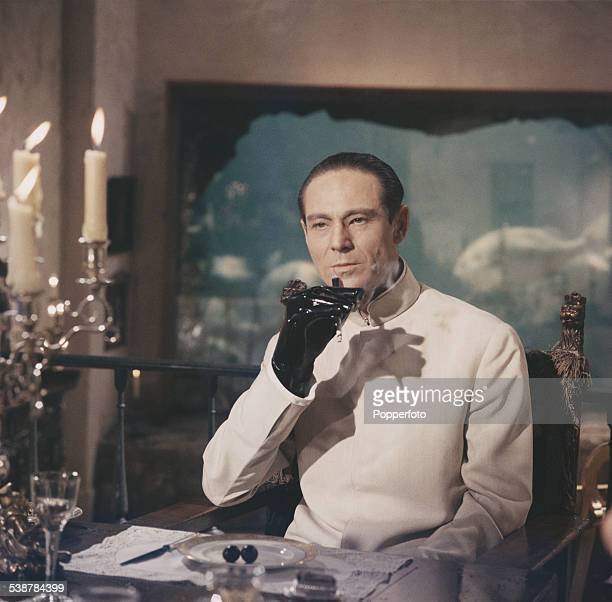 Canadian actor Joseph Wiseman pictured dressed in character as Dr Julius No wearing a latex glove and smoking a cigarette in a dining room scene from...